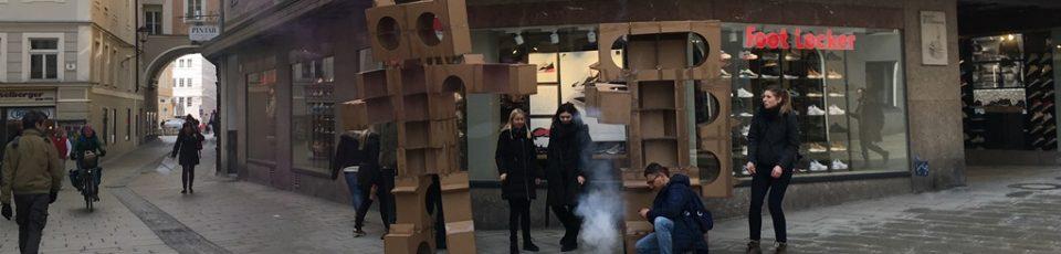 Das Foto zeigt Studierende mit Kartonmonstern in der Linzergasse.