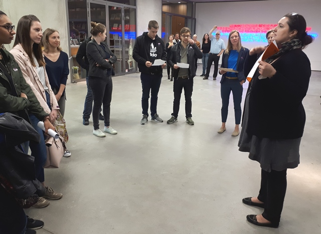 Das Bild zeigt die Kuratorin Tina Teufel im Museum der Moderne mit Studierenden