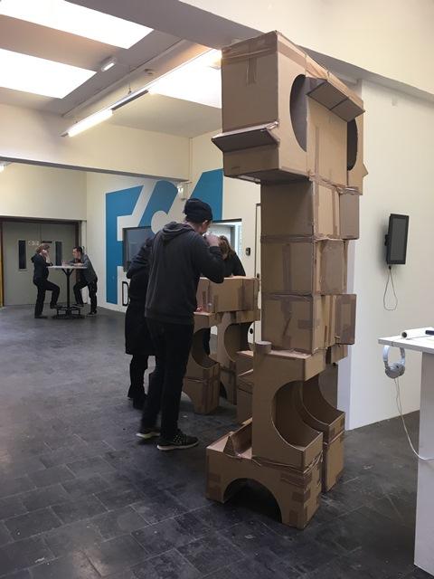 Das Bild zeigt Teilnehmende des Monster-Workshop, die große Monster aus Karton bauen.