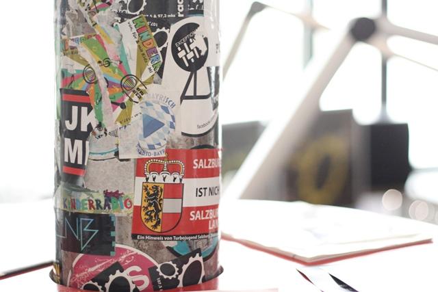 Das Bild zeigt eine mit Stickern beklebte Säule im Sendestudio der Radiofabrik