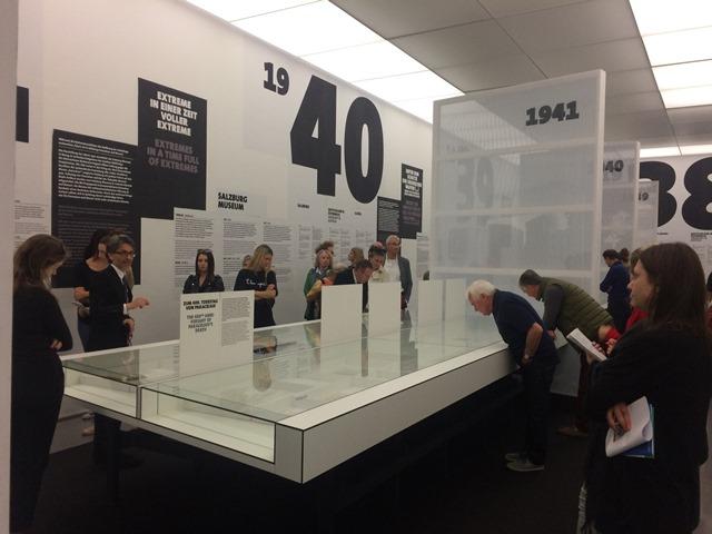 Das Bild zeigt Besucher der Ausstellung Anschluss Krieg und Trümmer bei Vitrinen mit Bildern und Texttafeln