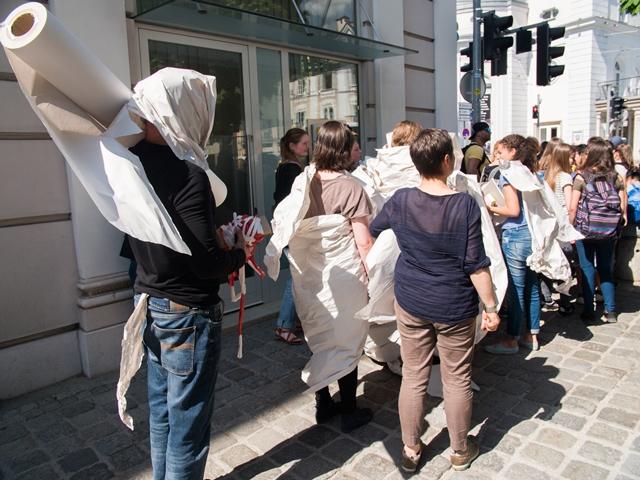 Die Workshopteilnehmer gehen vom Makartsteg in die Bergstraße und sind teilweise in Papierbahnen gehüllt