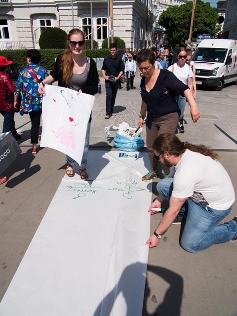 Die Papierrolle auf dem Makartsteg wird von den Workshopteilnehmerinnen beschriftet