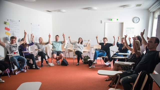 Die TeilnehmerInnen am Workshop mit Christina Laabs sitzen im Kreis und heben die Hände in die Höhe