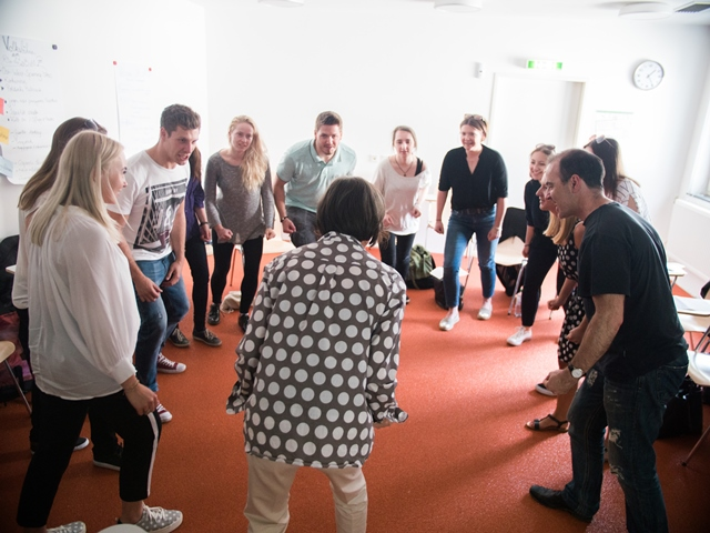 Die Teilnehmer am Workshop mti Christina Laabs machen im Kreis stehend Übungen.
