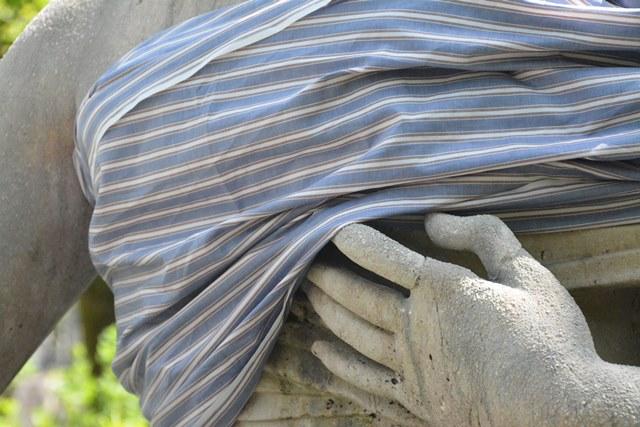 Fotografische Inszenierung als Intervention im Salzburger Stadtraum. eine Statue ist in ein Tuch gehüllt, man sieht Hand und Schulter.