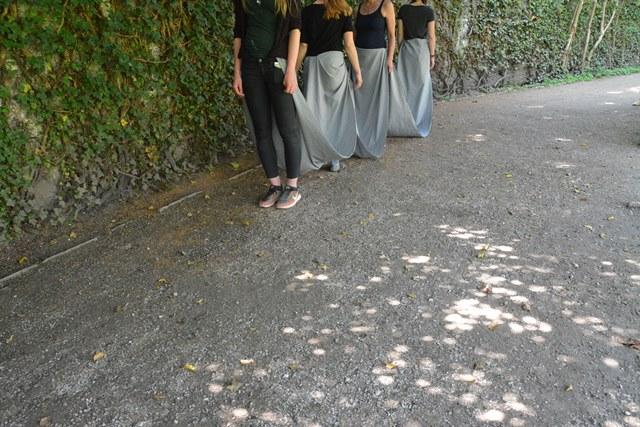Fotografische Inszenierung als Intervention im Salzburger Stadtraum. Vier Personen stehen hintereinander und sind durch ein Tuch miteinander verbunden.