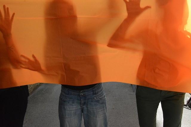 Fotografische Inszenierung als Intervention im Salzburger Stadtraum: ein oranges Tuch verhüllt Personen