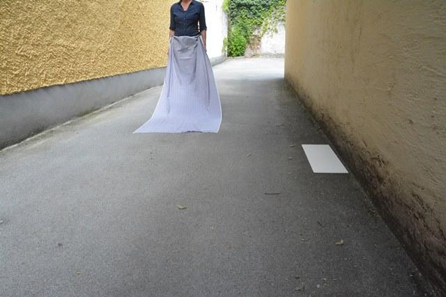 Fotografische Inszenierung als Intervention im Salzburger Stadtraum. Eine Person ist halb von einem Tuch verhüllt.