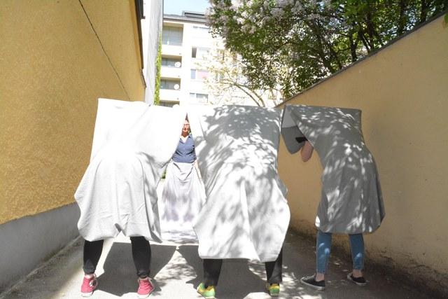 Fotografische Inszenierung als Intervention im Salzburger Stadtraum. Vier Personen formen mit Tüchern eine Skulptur.