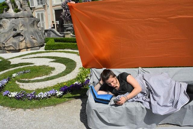 Fotografische Inszenierung als Intervention im Salzburger Stadtraum. Eine Person liegt mit Tüchern auf einer Bank im Mirabellgarten wie in einem Wohnzimmer