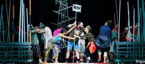 Das Bild zeigt einen Ausschnitta aus einem Theaterstück, in dem es um Migration geht.