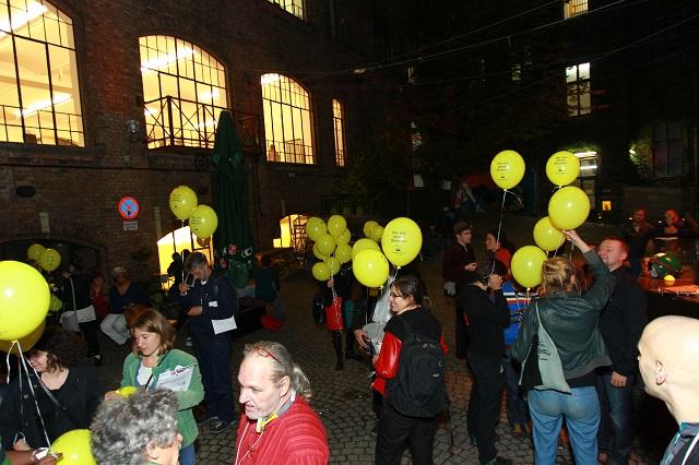 das Bild zeigt Personen mit gelben Luftballons die am Projekt Wahlwexel teilnahmen