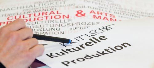 Eine Hand mit einem Stift zeigt auf den Schriftzug kritische kulturelle Produktion