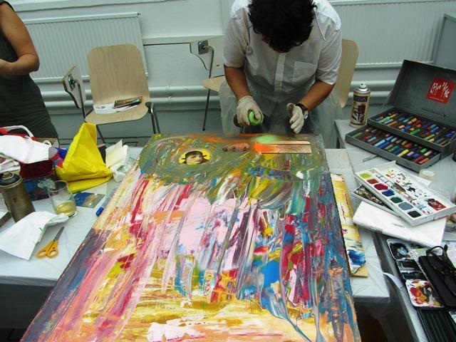 Das Bild zeigt eine Teilnehmerin, die eine Collage mit Farbspray bearbeitet.