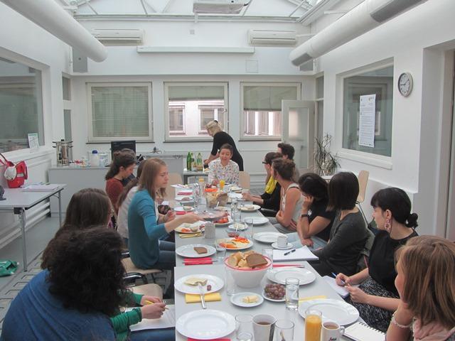 Die Stipendiatinnen der PART Akademie sitzen rund um einen Tisch beim Frühstück.