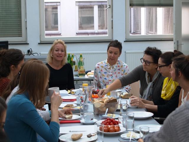 Sieben Personen sitzen beim Frühstück.