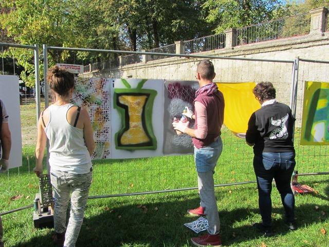 Drei Personen arbeiten an unterschiedlichen Buchstaben, die mit Farbspray auf Kartons gesprüht wurden.