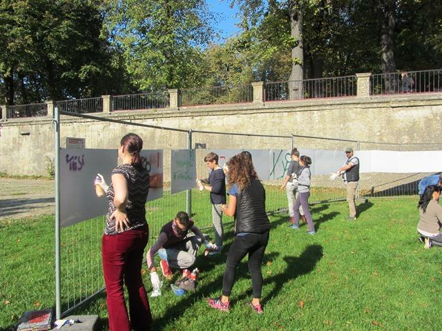 Auf dem Bild sind mehrere Personen zu sehen, die im Freien große Kartons mit Farbe besprühen.