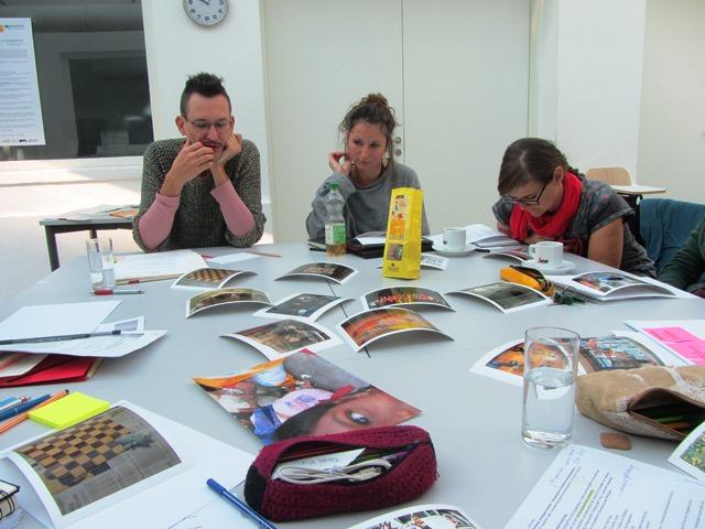 Das Bild zeigt 3 Studierende an einem Tisch mit Fotos