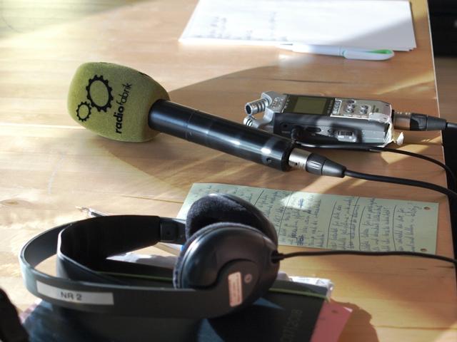 Das Bild zeigt Kopfhörer, ein Aufnahmegerät und ein Mikrofon mit dem Logo der Radiofabrik
