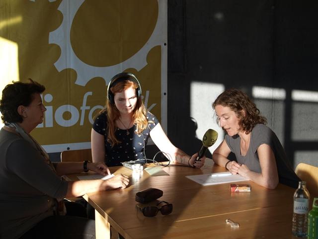 3 teilnehmerinnen sitzen an einem Tisch, eine hat ein Mikrofon in der Hand und Kopfhörer auf. Eine spricht in das Mikro