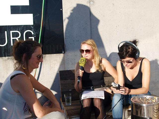 Das Bild zeigt 3 Teilnehmerinnen, eine mit Kopfhörer, eine mit Mikrofon