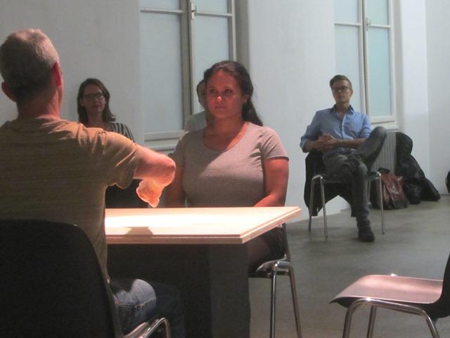 Sandra Chatterjee und Chris Lechner sitzen sich an einem Tisch gegenüber