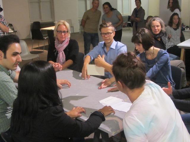 Das Publikum sitzt an Tischen und bekommt Anweisungen auf Karten