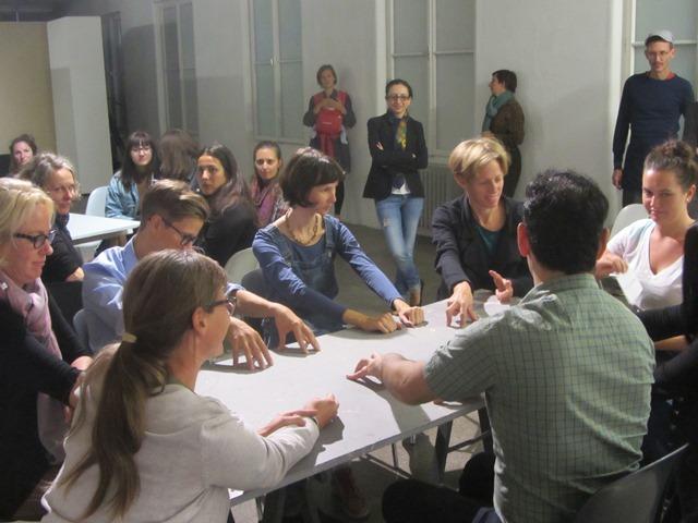 6 Personen sitzen um einen Tisch und haben ihre Hände auf dem Tisch.