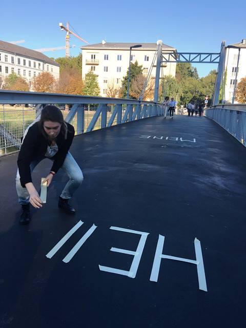 Nina Krebs beklebt den Makartsteg mit einem Schriftzug. Zu lesen ist MEINE