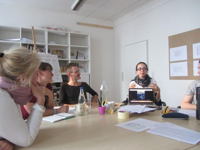 Die Teilnehmerinnen sitzen im Kreis. Eine zeigt auf dem Laptop ein Foto von der Beschriftung des Makartstegs.