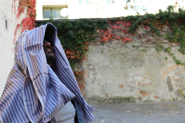 Ein Mann ist in ein gestreiftes Tuch gehüllt und steht vor einer Mauer.