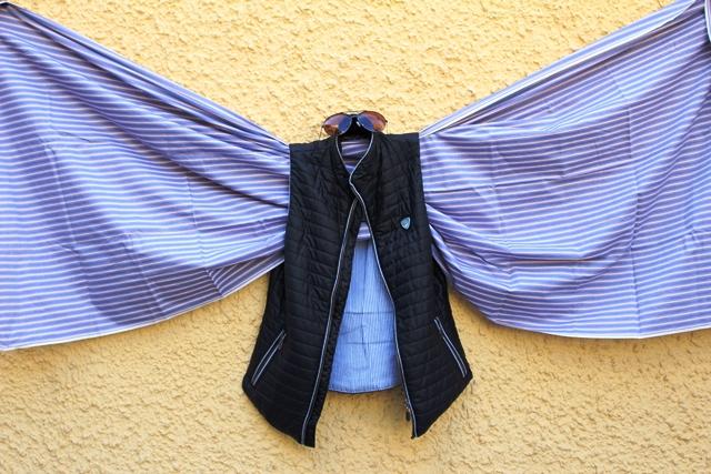 Eine ärmellose Jacke, obendrauf eine Sonnenbrille, aus den Ärmeln schaut links und rechts ein Tuch heraus, es sieht aus wie Flügel.