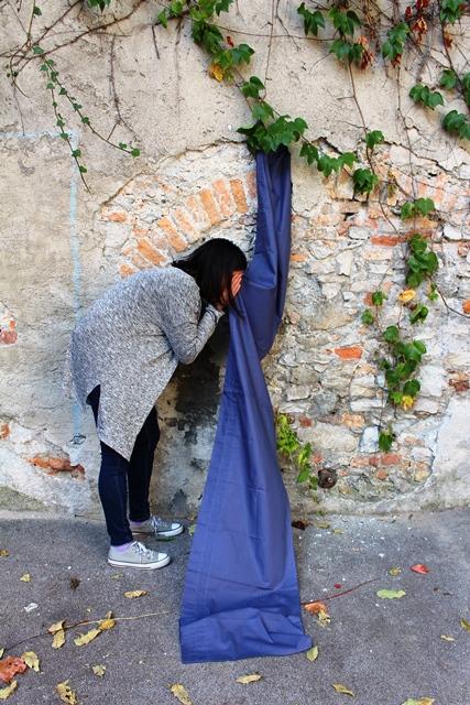 Ein Tuch hängt vor einer Mauer, eine Person steht gebückt daneben und versteckt ihr Gesicht im Tuch.
