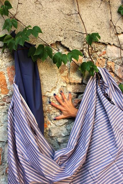 2 verschiedenen Tücher sind vor eine Mauer drapiert, unter einem Tuch schaut eine Hand hervor.