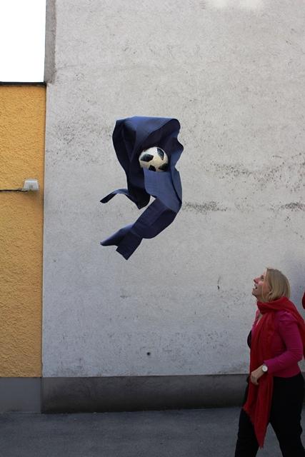 Eine Frau schaut auf ein Tuch und einen Ball, die in der Luft fliegen