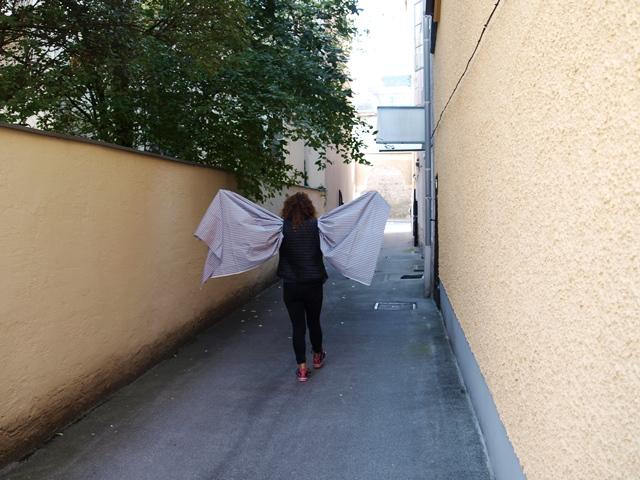 Eine Frau hat ein Tuch um ihre Arme drapiert und hält sie seitlich weggestreckt.