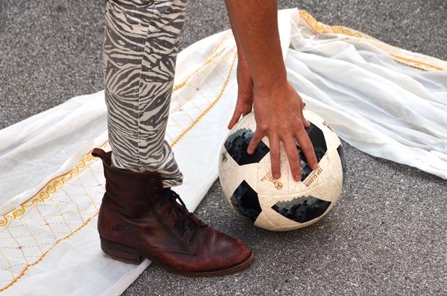 Ein Fuß, 2 hände, ein Fußball, im Hintergrund ein Tuch.