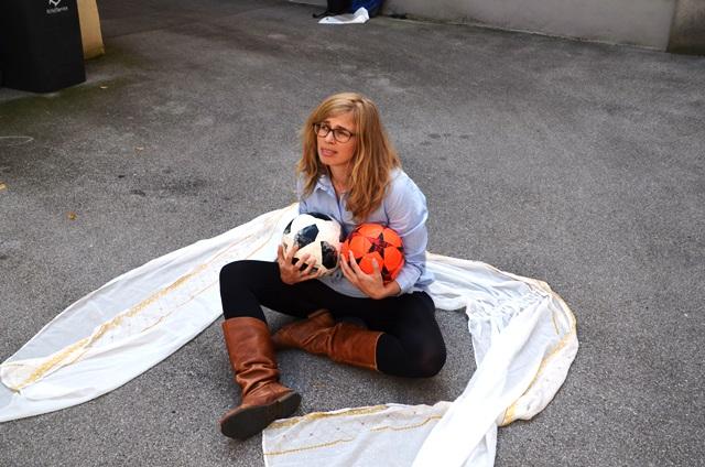 Eíne Frau mit 2 Fußbällen sitzt auf dem Boden, im Freien, rund um sie ist ein tuch drapiert.