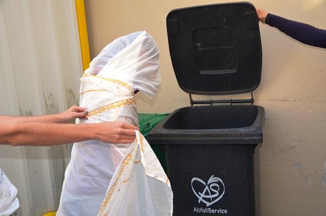 Ein mit einem Tuch verhüllter Gegenstand wird von 2 Händen gehalten, im Hintergrund eine offen Mülltonne,