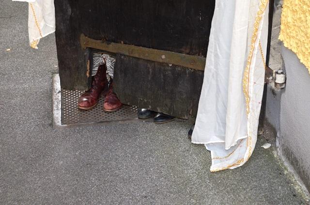 Eine offene Holztür, dahinter vier Füße, ein Tuhc