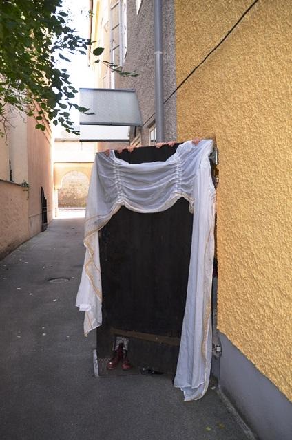 Eine Holztür über die ein Tuch gehängt ist, oben sind hände zu sehen.