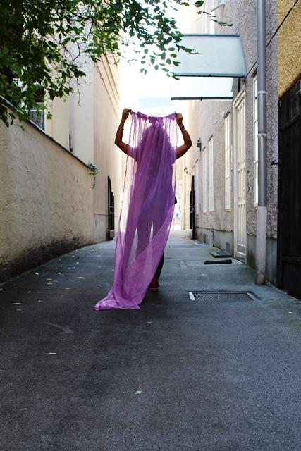 Eine Person, die in ein leicht transparentes Tuch gehüllt ist steht in einer engen Gasse