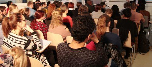Ein großer Raum mit Sesselreihen und vielen Menschen bei einem Vortrag