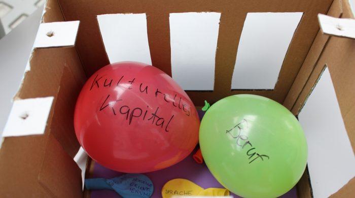 Eine Schachtel, in die Fenster geschnitten sind, darin Luftballons mit unterschiedlichen Größen und Beschrifttungen: Beruf, Kulturelles Kapital, Sprachen, sexuelle Orientierung