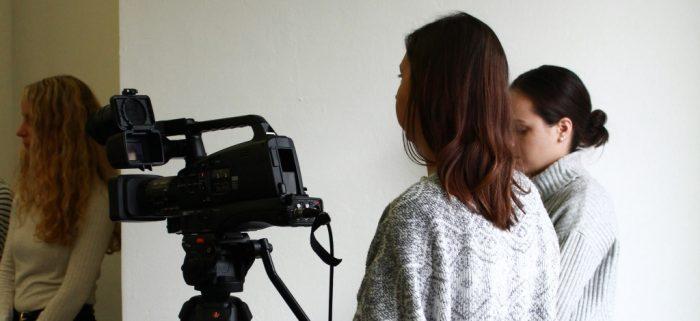 2 Studierende stehen hinter einer Videokamera