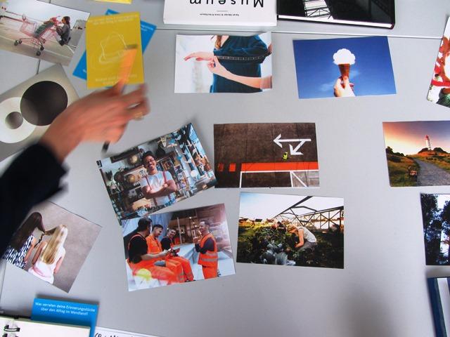Das Bild zeigt Fotos die auf einem Tisch liegen und Beispiele für Corporate Design für Kulturprojekte zeigen