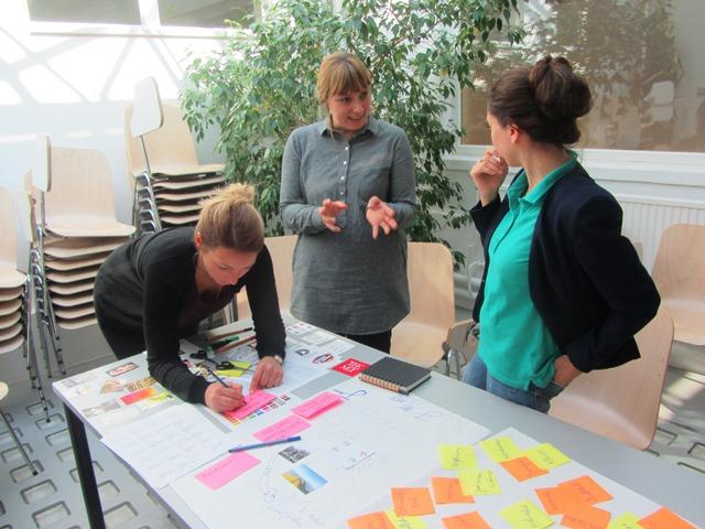 Das Bild zeigt 3 Personen, die an einem Tisch schreiben bzw. reden.