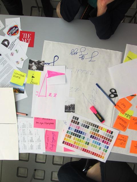 Im Bild sind Arbeitsmaterialien rund um den Schriftzug Jazz zu sehen. Das A in Jazz ist ein großes spitzes Dreieck